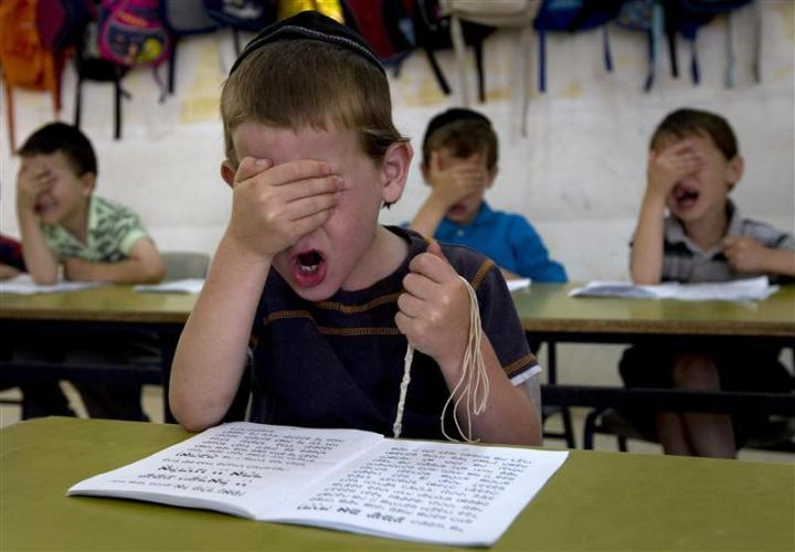 Ultra Orthodox students gesture as they pray during a reading class at the Kehilot Yaacov Torah School for boys in Ramot